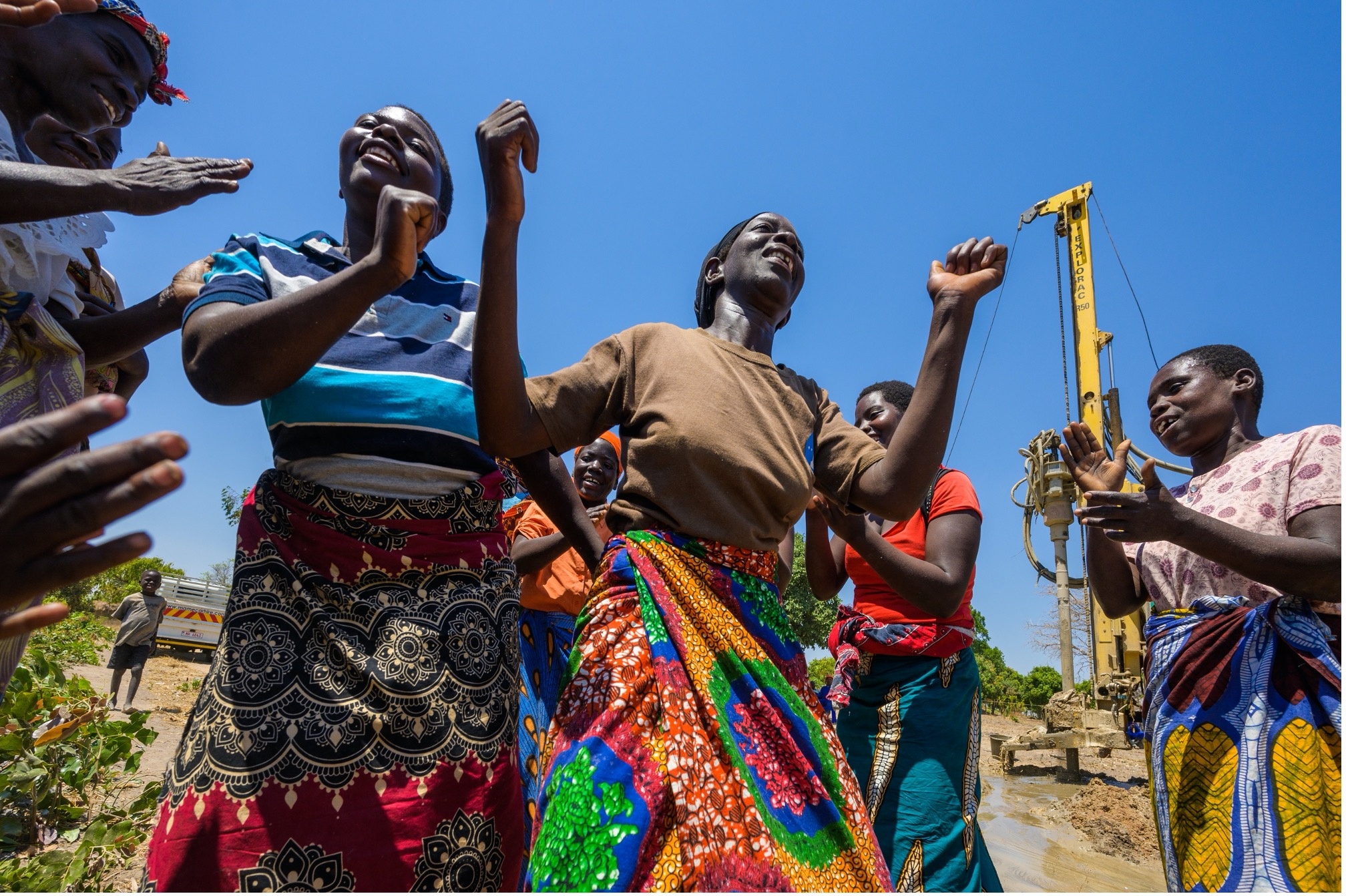 Women celebrating a borehole bringing clean water to their community in Mpondagaga, Malawi. (©2019 World Vision/photo by Jon Warren)