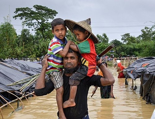 Abdul and his two sons are leaving Balukhali Refugee Camp in Bangladesh after spending a long odious night in the tent filled with rainwater.