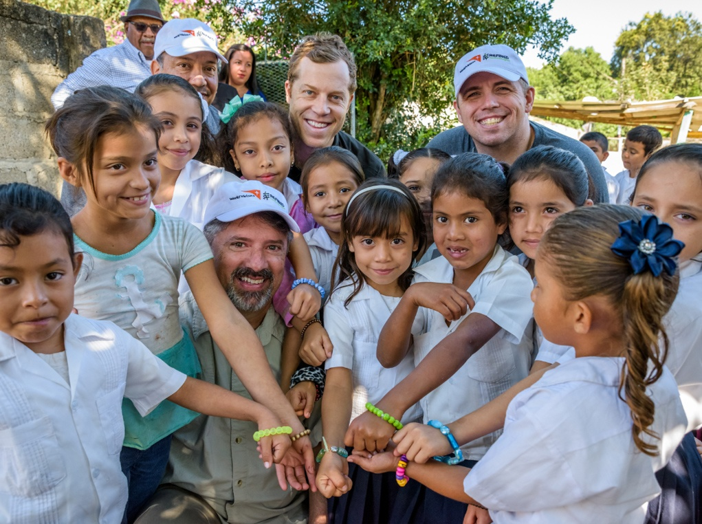 Children from a school which received clean water through RTI funding show off handmade bracelets they received from the team.