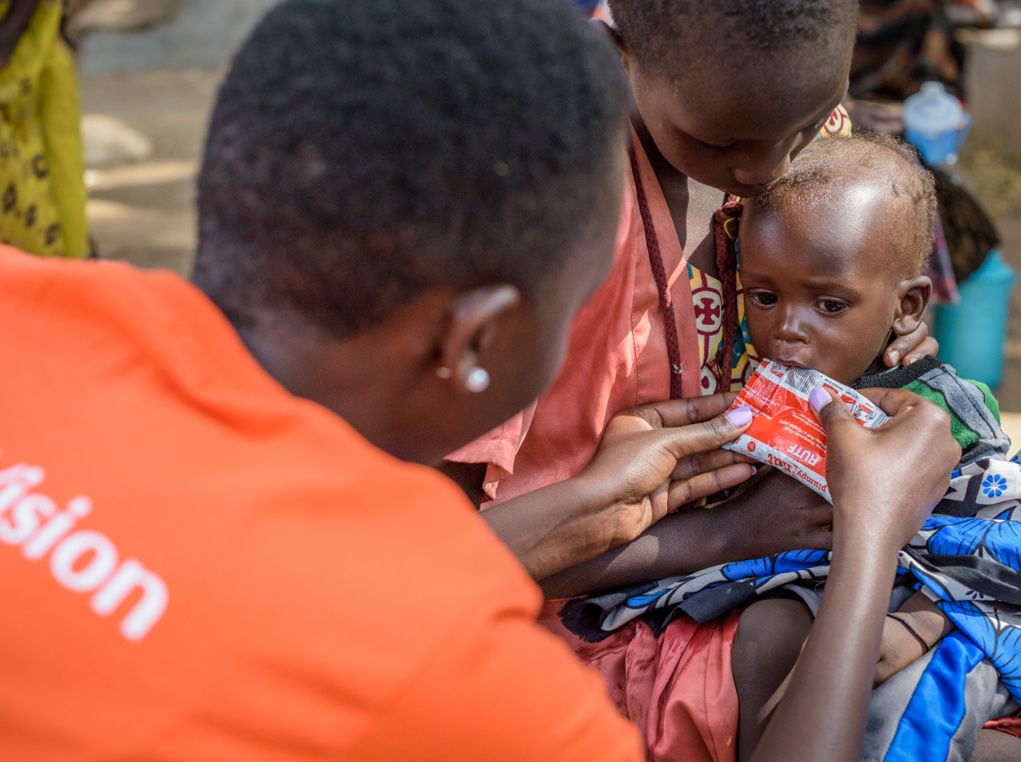 World Vision staff nutritionist, June Cherutich gives baby Akusi, 9 months, Ready to Use Therapeutic Food (RUTF) after finding that she is severely malnourished.
