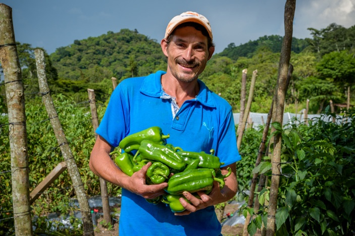 Honduran farmer who is part of the THRIVE program holding some of his harvest