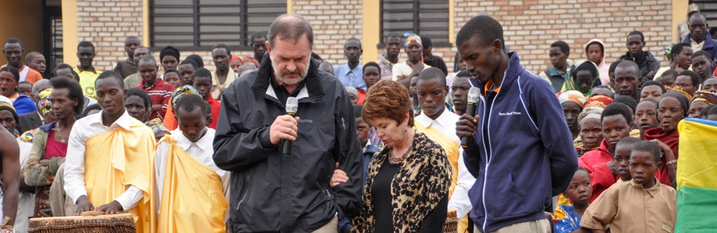 The Phillips praying during the dedication of the new vocational center in Rwanda