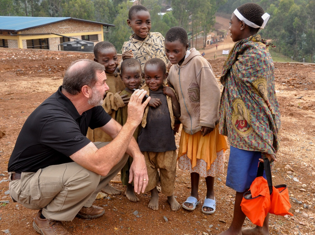 Stu playing with children in front of the new vocational center in Rwanda