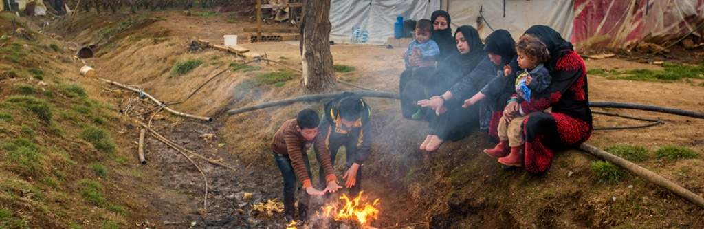 A Syrian refugee family in Lebanon warms themselves by a fire in a ditch in front of their tents, burning garbage -- mostly plastic -- to stay warm.