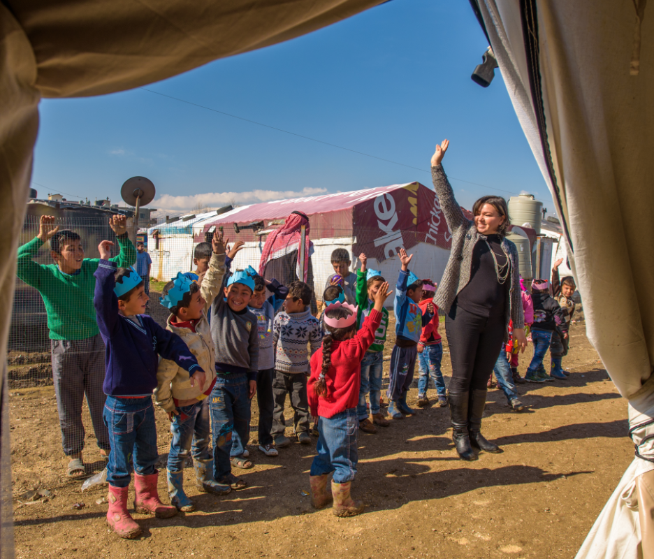 Syrian refugee teacher, Wafaa, (a former public school teacher) and her class play a game of follow the leader at World Vision's Early Childhood Education program in Lebanon.